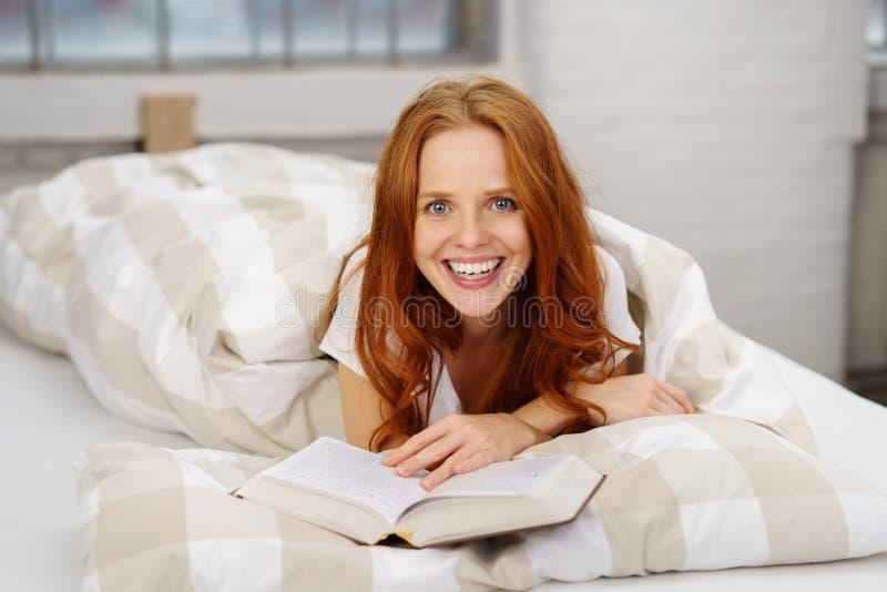 Giovane donna emozionante che si rilassa a letto con un libro fotografia stock