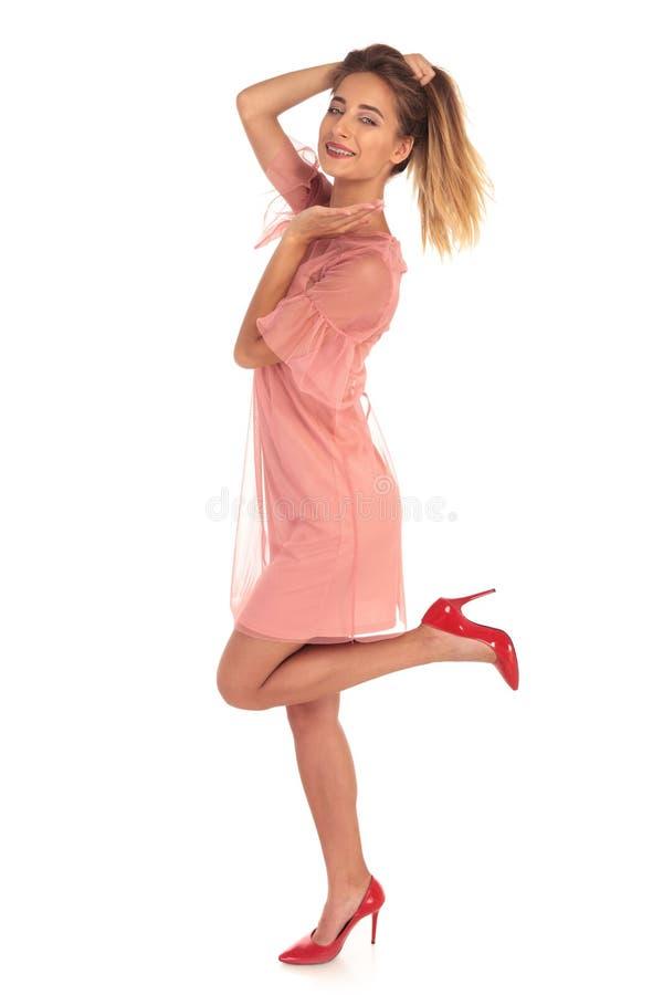Giovane donna emozionante che tiene i suoi capelli ed un vantaggio fotografia stock libera da diritti