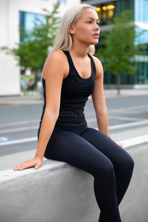 Giovane donna esaurita attraente che riposa durante il suo allenamento in città immagine stock