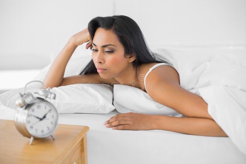 Giovane donna esaurita che si trova nel suo letto immagini stock
