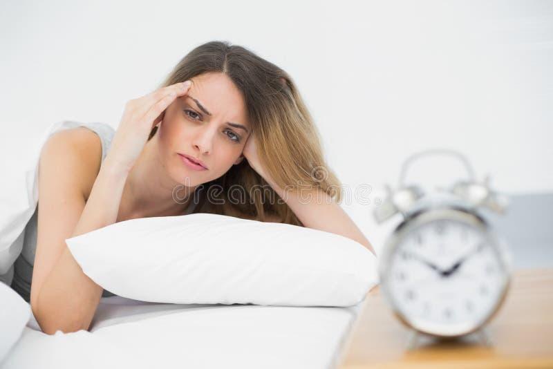 Giovane donna esaurita che si trova nell'ambito della copertura sul suo letto immagine stock libera da diritti