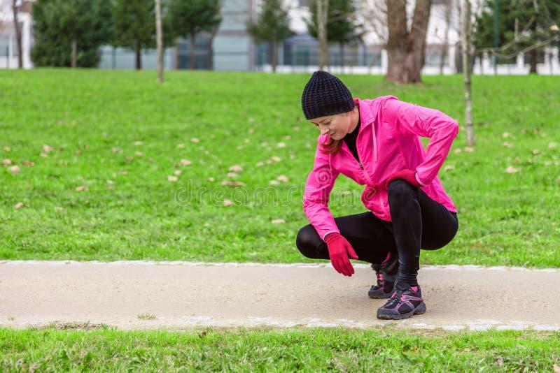Giovane donna esaurita dopo il treno un giorno di inverno freddo sulla pista di addestramento di un parco urbano fotografia stock libera da diritti