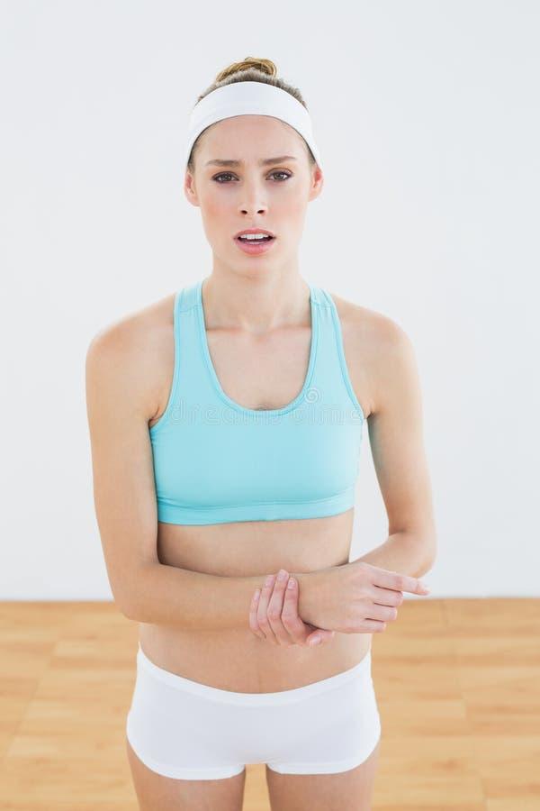 Giovane donna esile in abiti sportivi che toccano il suo polso danneggiato fotografia stock