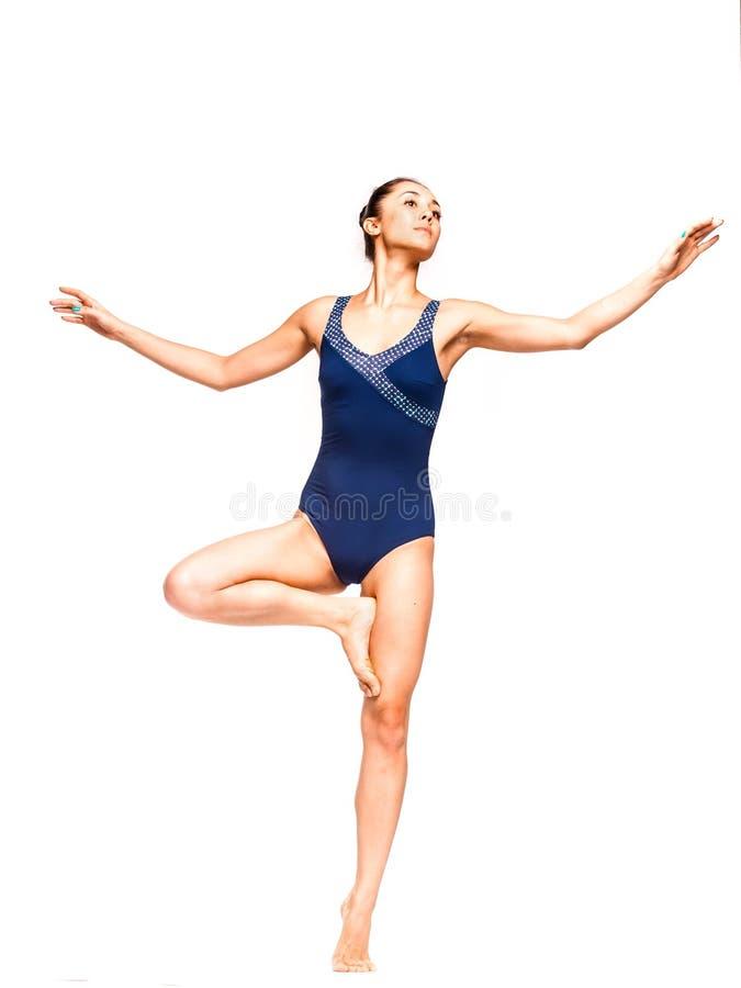Giovane donna esile che equilibra su un piede fotografia stock