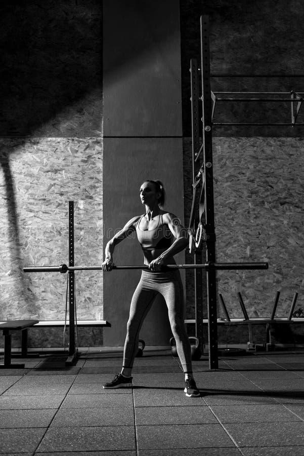 Giovane donna esile che si esercita con una barra di metallo lunga fotografie stock
