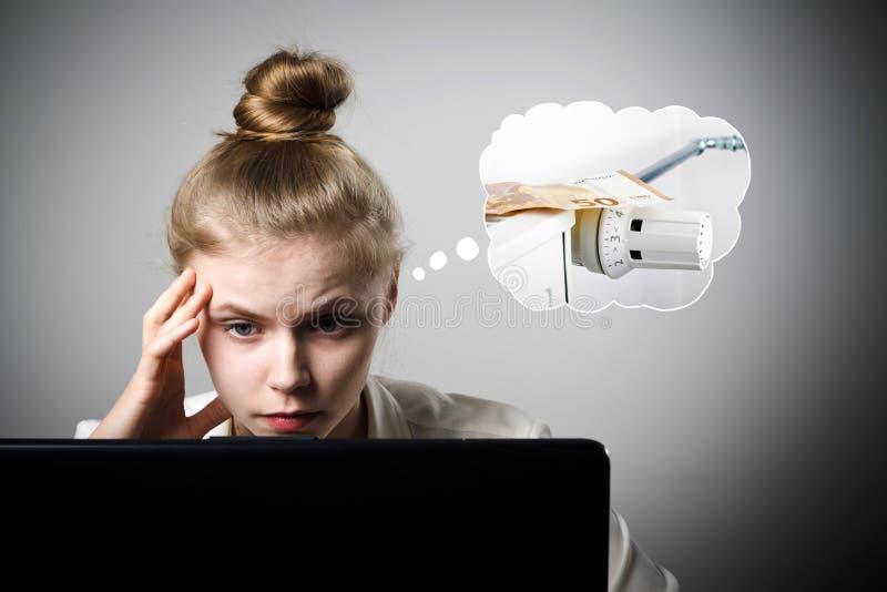 Giovane donna esile con il computer portatile Periodo di riscaldamento, tasse e concetto di risparmio radiatore fotografia stock libera da diritti
