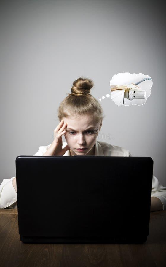 Giovane donna esile con il computer portatile Periodo di riscaldamento, tasse e concetto di risparmio radiatore immagine stock libera da diritti