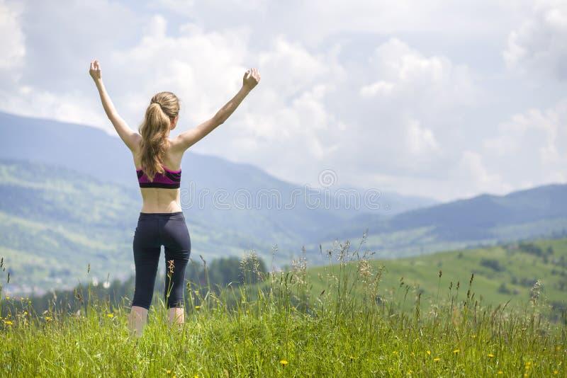 Giovane donna esile con le armi alzate all'aperto su fondo di bello paesaggio della montagna il giorno di estate soleggiato immagine stock libera da diritti