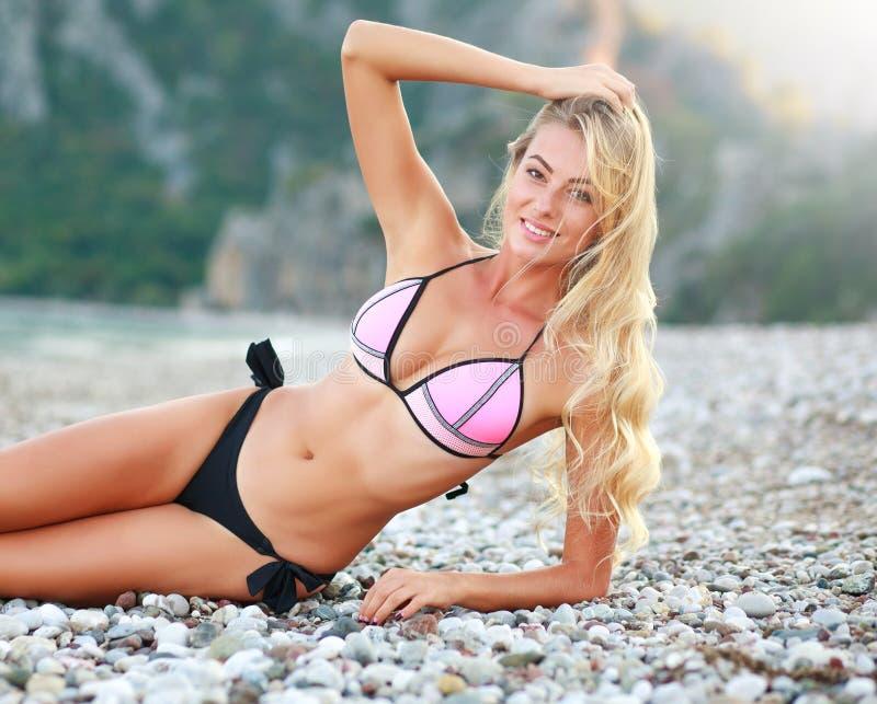 Giovane donna esile sensuale felice che si trova sulla spiaggia in bikini immagini stock