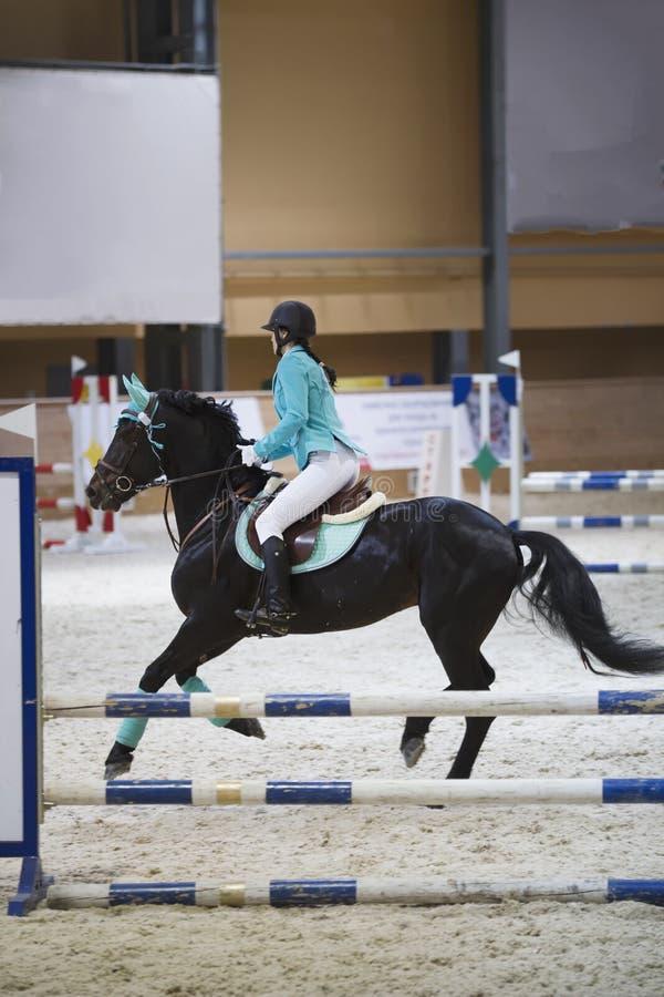 Giovane donna esile sul cavallo nero che galoppa alla concorrenza di salto di manifestazione immagini stock libere da diritti