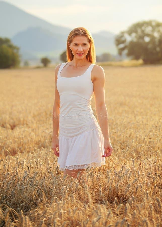 Giovane donna esile in vestito bianco che sta nel giacimento di grano nel sunse immagini stock