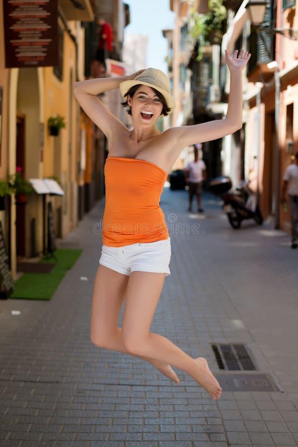 Giovane donna esuberante che salta per la gioia fotografie stock libere da diritti