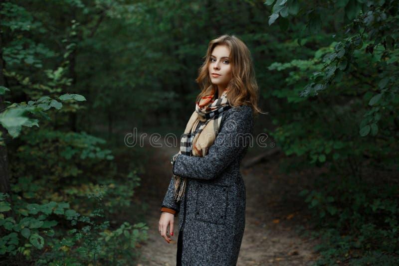 Giovane donna europea attraente graziosa in una sciarpa a quadretti alla moda nelle passeggiate nel bosco grige eleganti di un ca fotografia stock libera da diritti