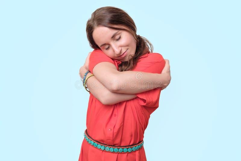 Giovane donna europea in vestito rosso che sta, sorridente ed abbracciantesi immagini stock