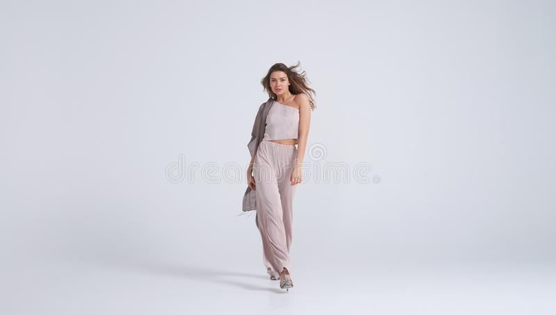 Giovane donna favolosa in attrezzatura alla moda che cammina verso la macchina fotografica immagini stock