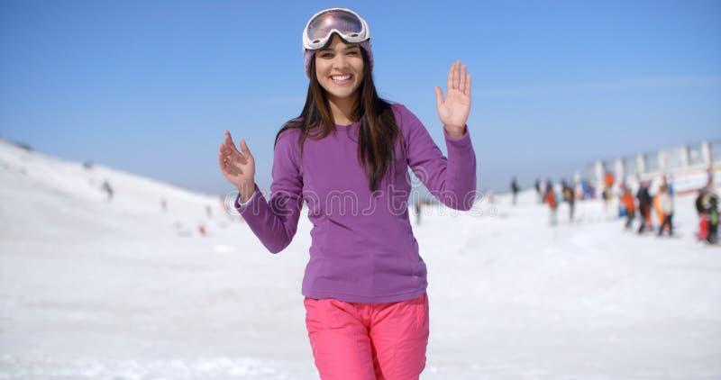 Giovane donna felice ad una stazione sciistica immagini stock libere da diritti