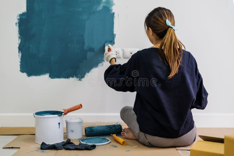 Giovane donna felice asiatica che dipinge parete interna con il rullo di pittura immagini stock