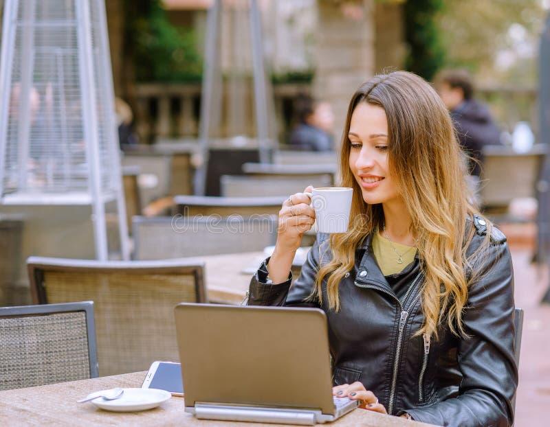 Giovane donna felice in attrezzatura alla moda che sorridono in caffè all'aperto e passare in rassegna moderna fotografia stock libera da diritti