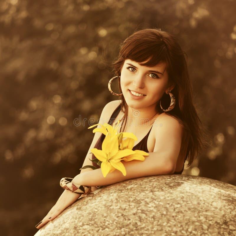 Giovane donna felice in canottiera sportiva marrone con i fiori immagine stock