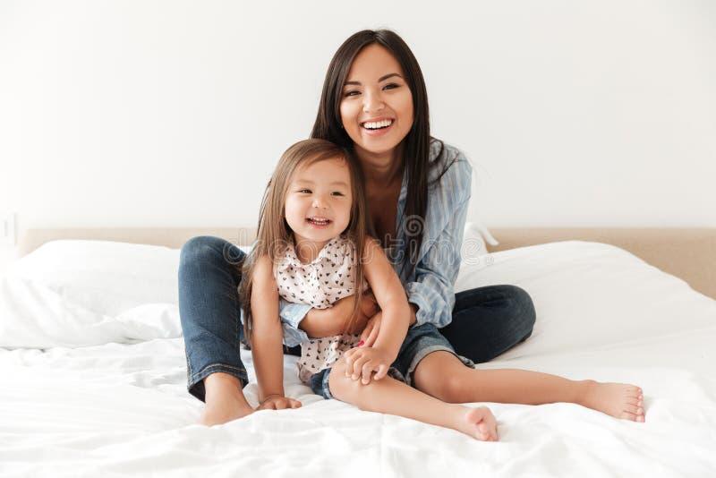 Giovane donna felice che abbraccia la sua piccola figlia fotografia stock