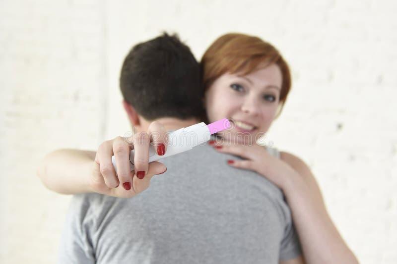 Giovane donna felice che abbraccia marito che tiene il test di gravidanza di risultato positivo che prevede un bambino immagini stock