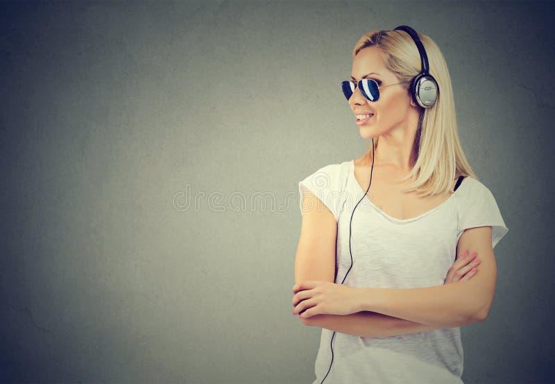 Giovane donna felice che ascolta la musica con le cuffie fotografie stock libere da diritti