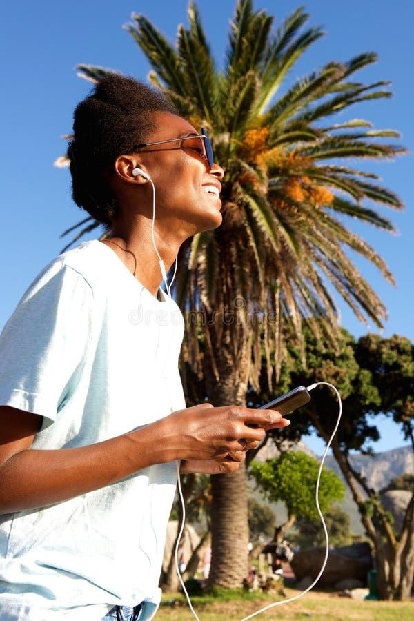 Giovane donna felice che ascolta la musica sulla spiaggia fotografia stock libera da diritti