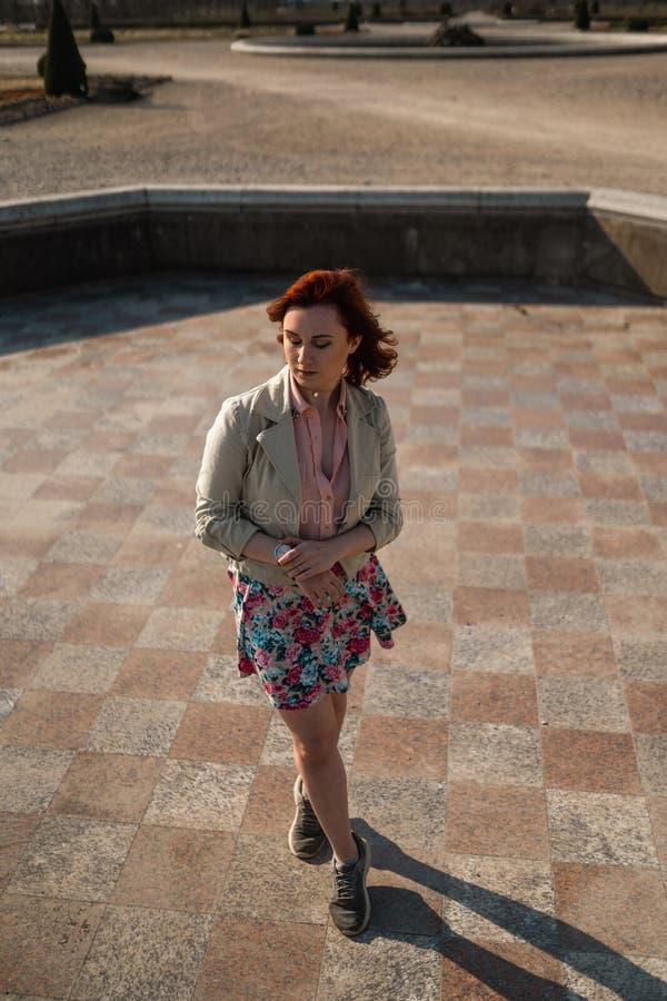 Giovane donna felice che balla in una fontana vuota che porta una gonna variopinta fotografia stock