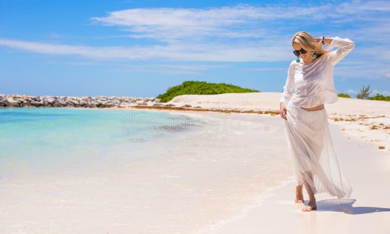 Giovane donna felice che cammina sulla spiaggia fotografia stock