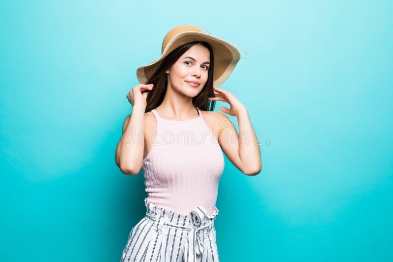 Giovane donna felice che cerca in cappello di paglia su fondo blu fotografia stock