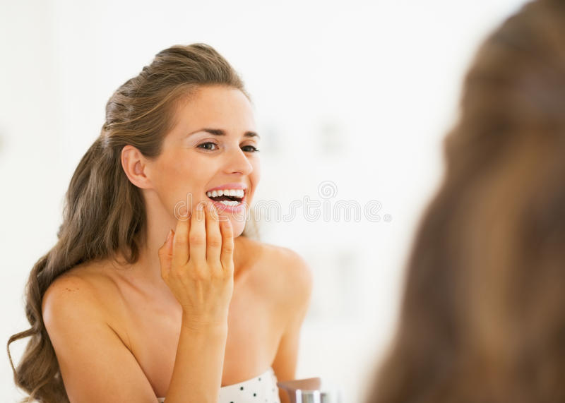 Giovane donna felice che controlla i denti in denti della doccia in specchio fotografie stock libere da diritti