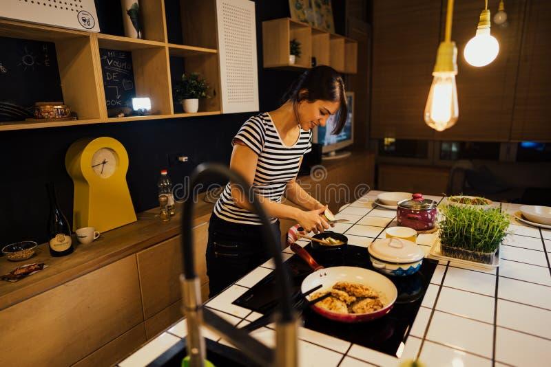 Giovane donna felice che cucina un pasto sano in cucina domestica Facendo cena sulla fresa facente una pausa di induzione dell'is immagini stock libere da diritti
