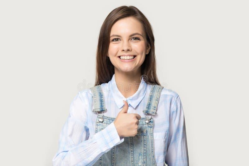Giovane donna felice che esamina macchina fotografica che mostra i pollici su immagini stock