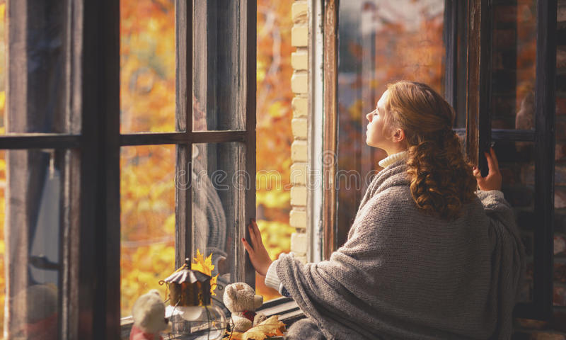 Giovane donna felice che gode dell'aria fresca di autunno alla finestra aperta fotografia stock libera da diritti