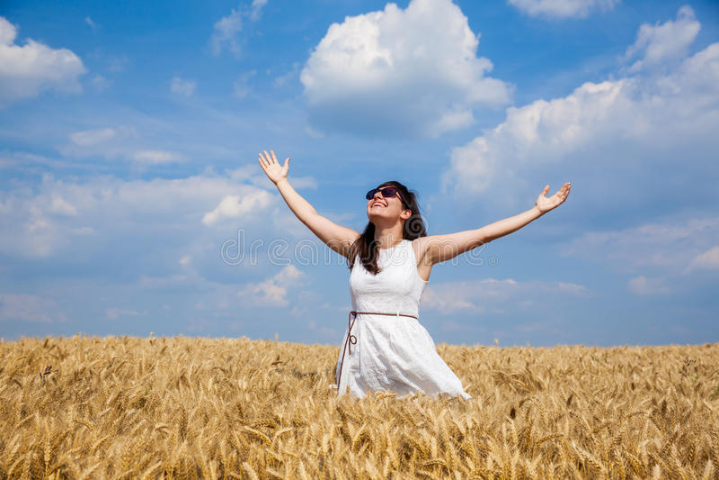 Giovane donna felice che gode della vita nel giacimento di grano dorato fotografie stock