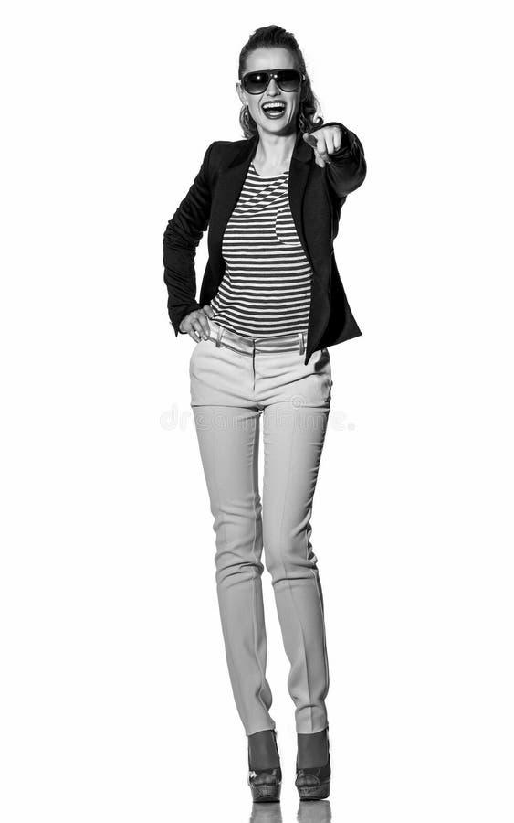 Giovane donna felice che indica in camera isolato su bianco immagine stock