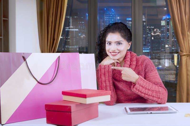 Giovane donna felice che indica i sacchetti della spesa fotografia stock