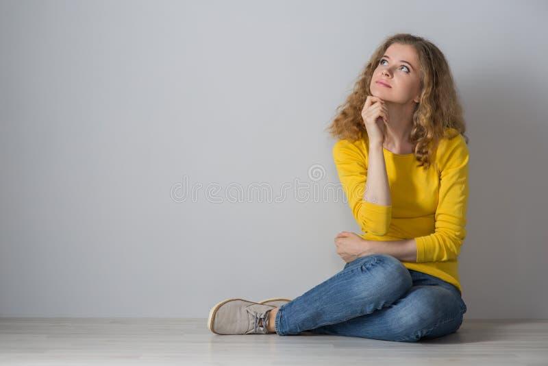 Giovane donna felice che indossa gli shorts gialli dei jeans e della camicia sopra il gr fotografia stock
