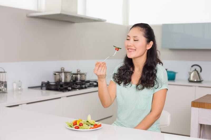 Giovane donna felice che mangia insalata in cucina fotografie stock