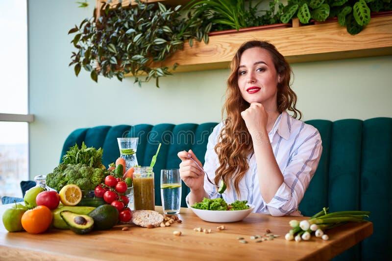 Giovane donna felice che mangia insalata nel bello interno con i fiori verdi sui precedenti e gli ingredienti freschi sulla tavol immagine stock