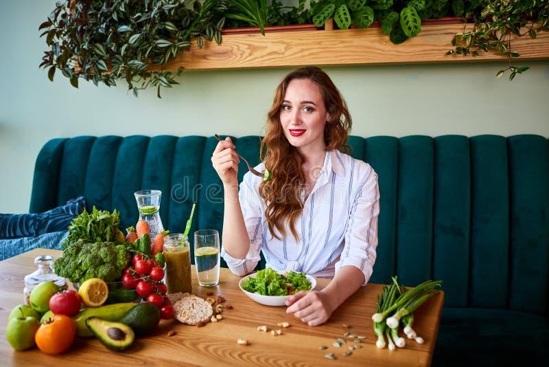 Giovane donna felice che mangia insalata nel bello interno con i fiori verdi sui precedenti e gli ingredienti freschi sulla tavol immagine stock libera da diritti