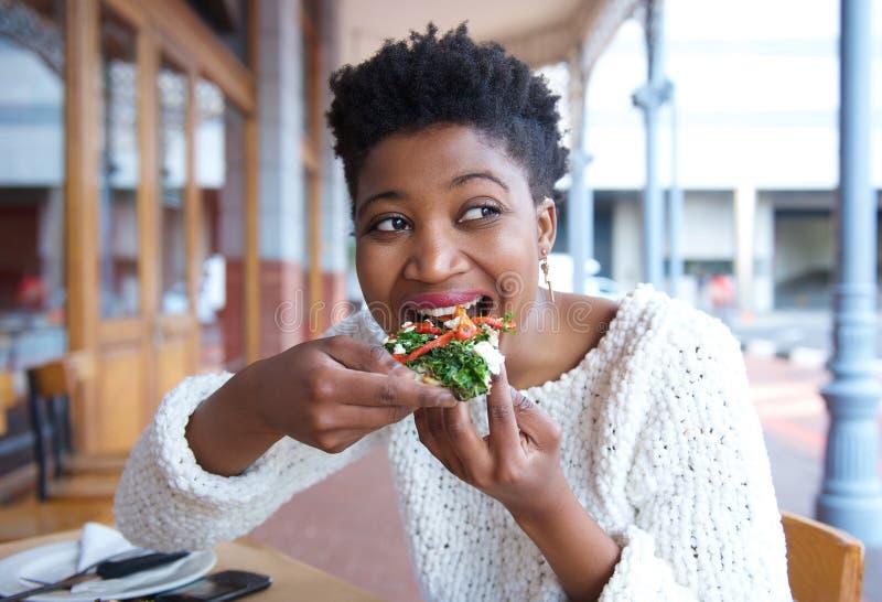 Giovane donna felice che mangia pizza al ristorante immagine stock libera da diritti