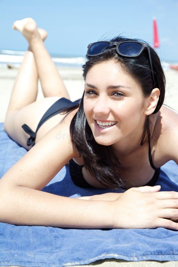 Giovane donna felice che mette su sorridere della spiaggia immagini stock libere da diritti