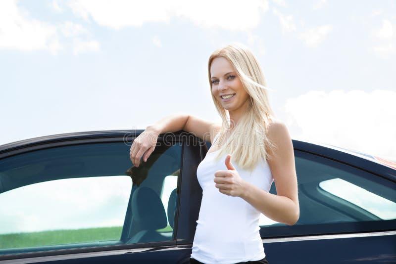 Giovane donna felice che mostra pollice sul segno immagini stock libere da diritti