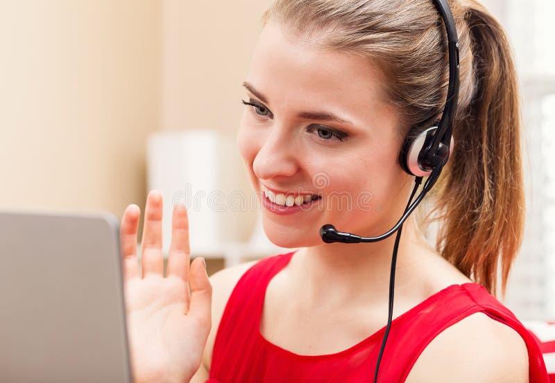 Giovane donna felice che parla sul suo computer portatile immagine stock libera da diritti