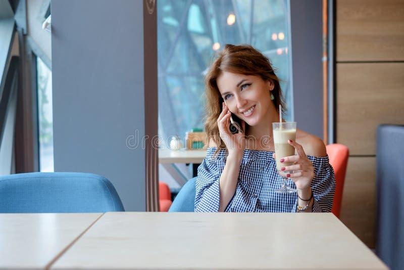 Giovane donna felice che parla sul telefono cellulare con l'amico mentre sedendosi da solo nell'interno moderno della caffetteria fotografia stock