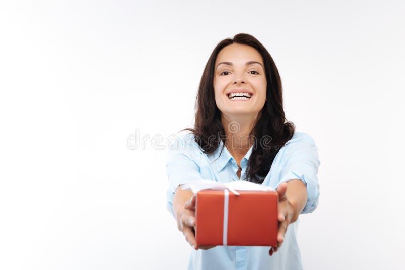 Giovane donna felice che passa un contenitore di regalo rosso immagine stock libera da diritti