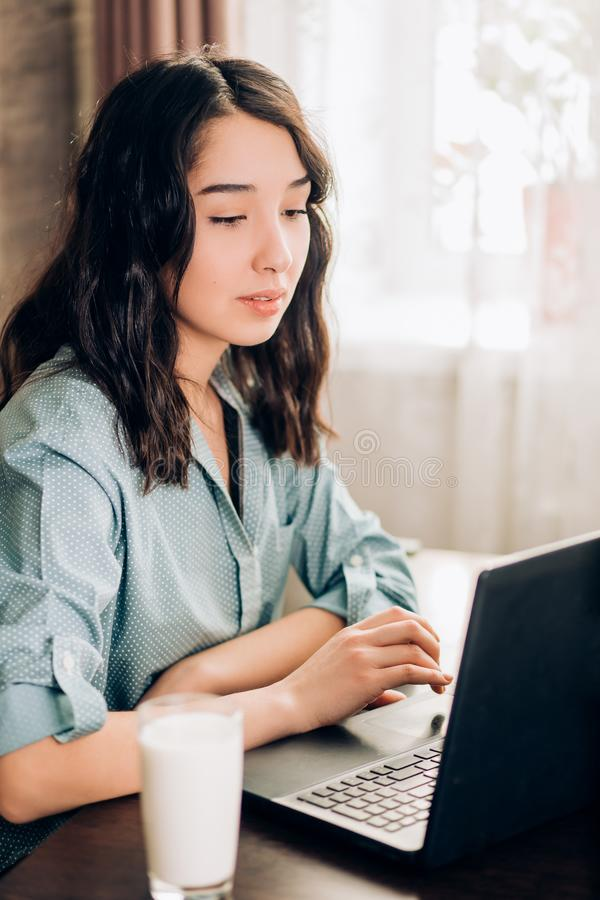 Giovane donna felice che per mezzo del computer portatile a casa fotografia stock