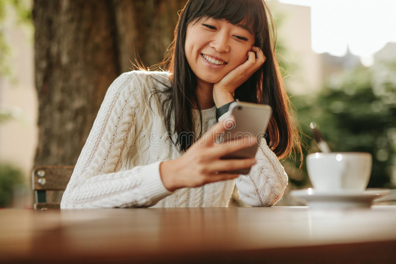 Giovane donna felice che per mezzo del suo cellulare al caffè fotografia stock libera da diritti