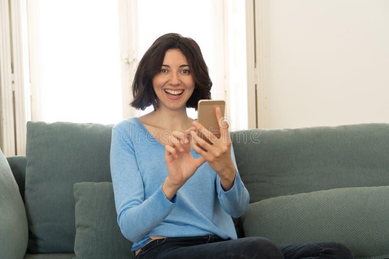 Giovane donna felice che per mezzo del suo Smart Phone che si siede sul sof? a casa Nello svago e nella dipendenza mobile fotografia stock